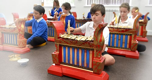 Children seated on the floor playing gamelan instruments